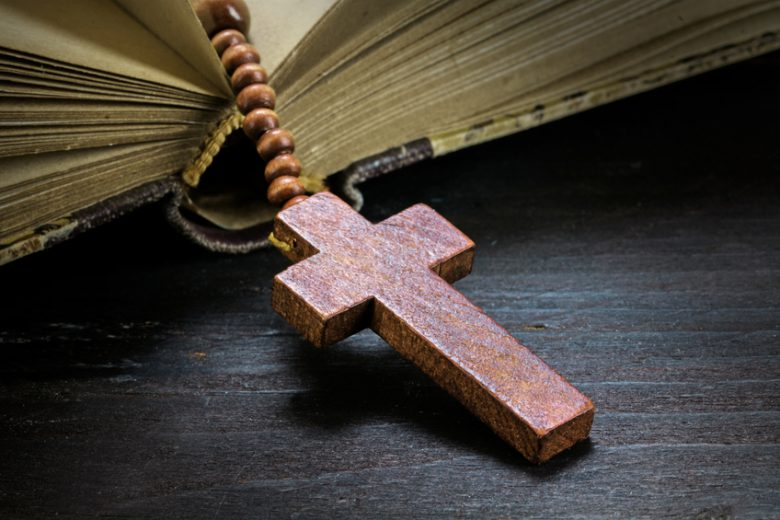 catholic wooden rosary beads with cross in an old book on dark rustic wood, religious symbol concept, toned with color filter, selected focus on christ, narrow depth of field